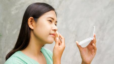 Asian women to apply pressed powder. Foto de archivo