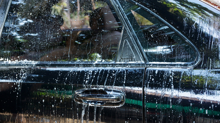 Washing a black car with high-pressure water. Stock Photo