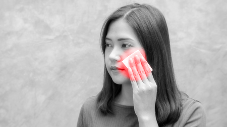women use an absorbent cotton on her face, black and white effect.