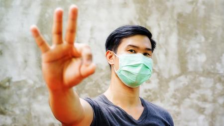 der Mann trägt eine Schutzmaske und hebt die Hand für ein OK-Symbol. Standard-Bild