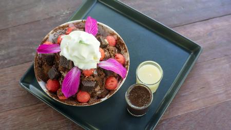Brownie and watermelon Bingsu dessert on a wooden table.