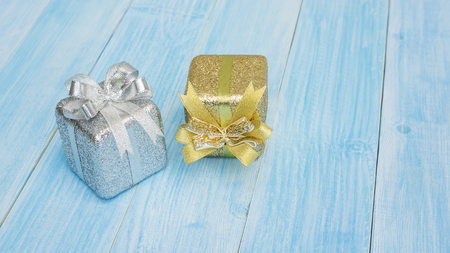 silver and gold gift box on a blue wooden table. Foto de archivo