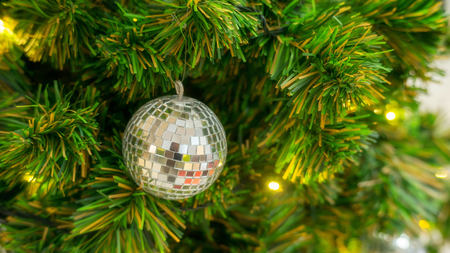 Golden and silver ball hanging on a Christmas tree.