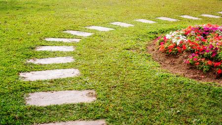 passerella di cemento in un giardino fiorito.