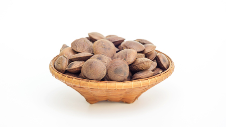 Sacha Inchi seeds in a basket on a white background.