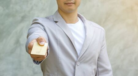 Man holding a card on a gray background.