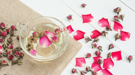 A cup of tea pink rose on a white wooden table.