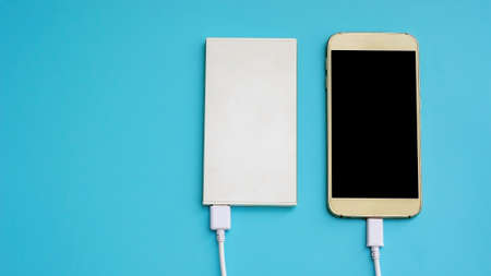 smartphone and power bank for charging mobile devices on a blue background.