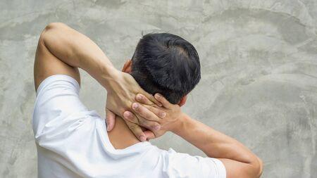 Men feeling pain in his neck on a gray background. Reklamní fotografie