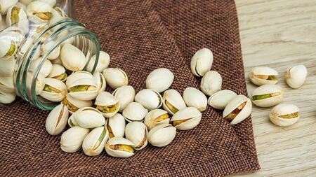 Pistachio nuts on a wooden table.