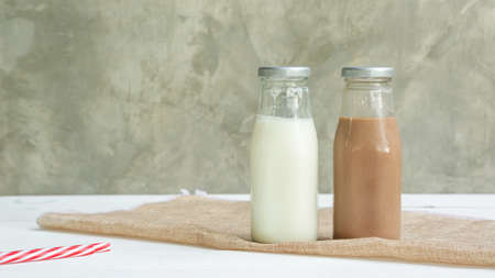 Milk and chocolate milk on a white wooden table. Stok Fotoğraf - 150623974