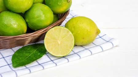 Green lime in a basket on a white wooden table.