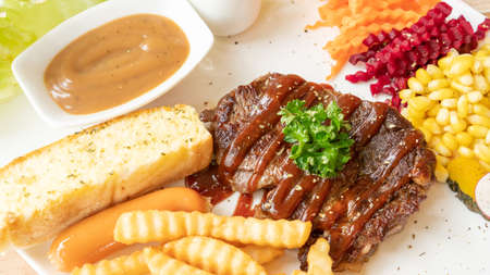 Beefsteak, French fries, and vegetable on a white plate. Stock fotó