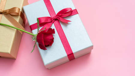Red rose and gift box on a pink background. Stock fotó