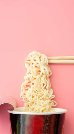 Instant noodles cup and chopsticks on a pink background.