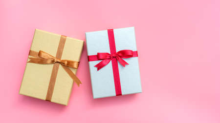 Silver and gold gift box on a pink background.