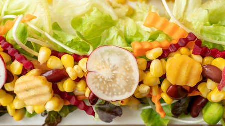 Corn, beetroot, carrot, red bean, and lettuce on a white plate. Stock fotó