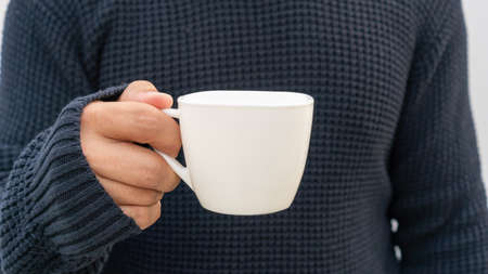 Man holding a white cup of coffee.