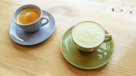 A cup of hot coffee and hot green tea on a wooden table in a morning.