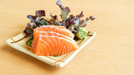 Fresh salmon sashimi on a wooden table.