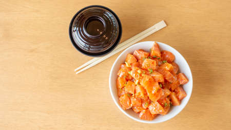 Fresh spicy salmon and rice on a wooden table.