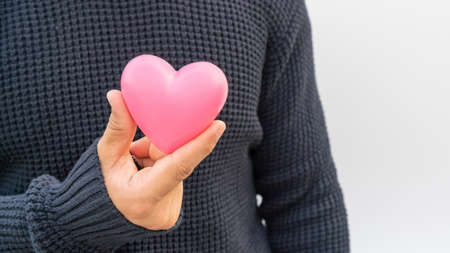 Man holding a pink heart on a white background.