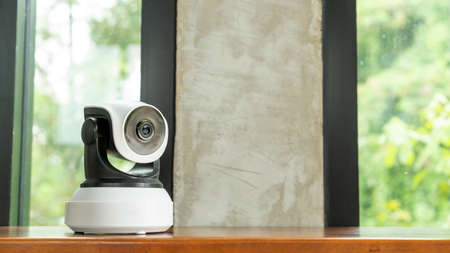 The security IP camera on a wooden table.