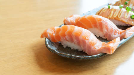 Fresh salmon sushi on a wooden table.