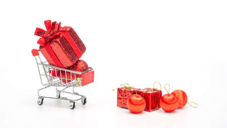 Red gift box in a shopping cart on a white background. 版權商用圖片