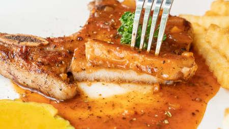 Pork Chop steak on a white plate.