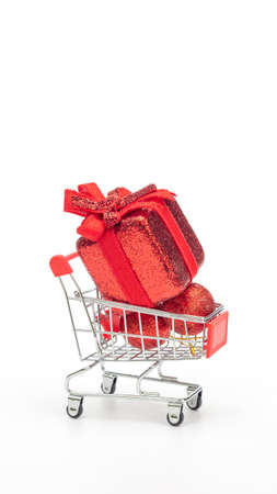 Red gift box in a shopping cart on  white