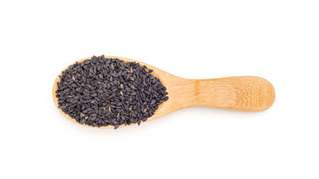 Black sesame seeds in a spoon on a white background. 免版税图像