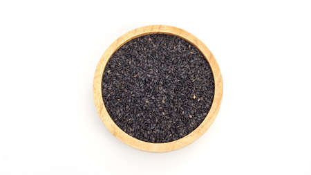Black sesame seeds in a bowl on a white background.
