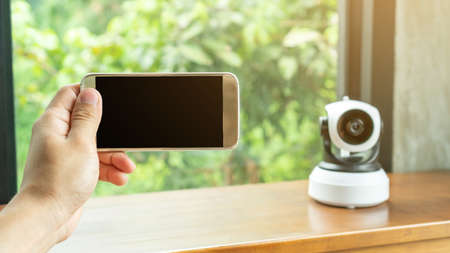 Smartphone connecting with security IP camera on a wooden table. 免版税图像
