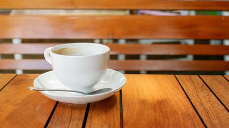 White cup of coffee on a wooden table. 免版税图像
