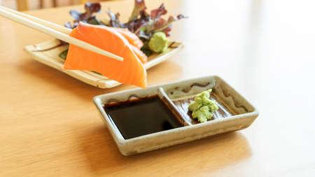 chopsticks tong fresh salmon sashimi on a wooden table. 免版税图像