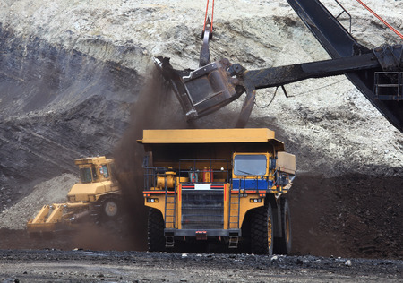 A haul truck is being loaded with dirt and ore at a mine site while another haul truck waits in the foreground