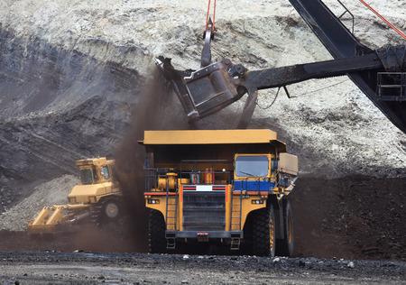 Un camion de transport est chargé avec de la terre et du minerai à un site de la mine, tandis qu'un autre camion de transport attend au premier plan Banque d'images