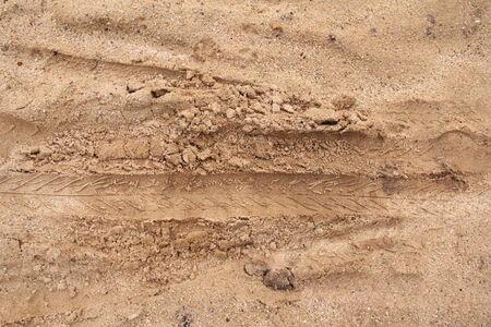 dirt on ground: vehicle wheel mark on dirt ground