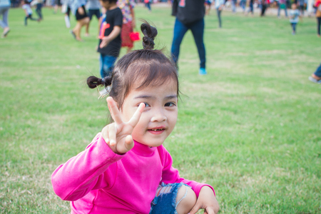 happy little girl sitting on green grass and playing in the park. soft focus. Imagens
