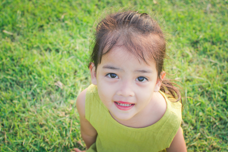 happy little girl sitting on green grass and playing in the park. soft focus. 版權商用圖片