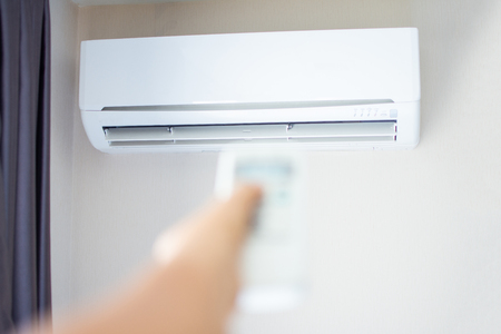 human hand press on remote control of Air Conditioner with hot weather. Subject is blurred.