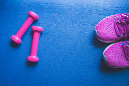 Fitness background, Equipment for gym and home dumbbell and Sneakers on color background. soft focus. Фото со стока