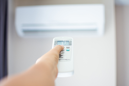 human hand press on remote control of Air Conditioner with hot weather. Subject is blurred. Stock Photo