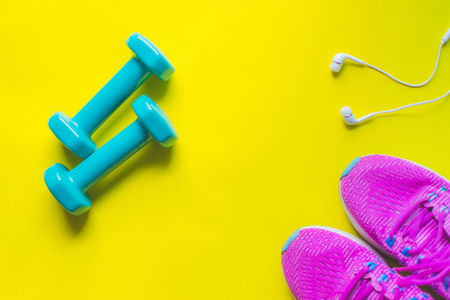 Fitness background, Equipment for gym and home dumbbell and Sneakers, earphone on color background. soft focus.