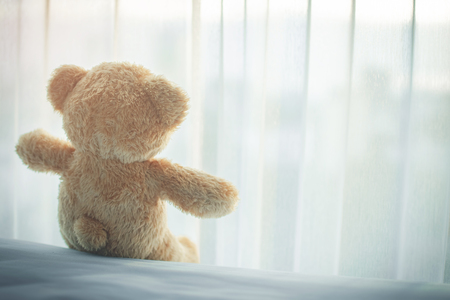 rear of lonely bear doll on bed room, feel like sad and low key. soft focus.