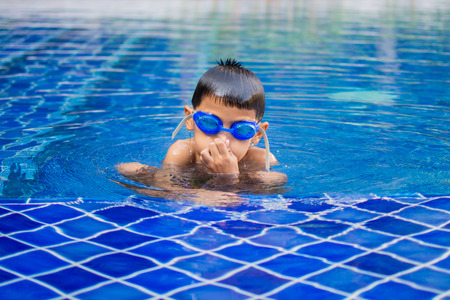 cute little boy feel happy play and swimming at swimming pool , sunny day and soft focus.