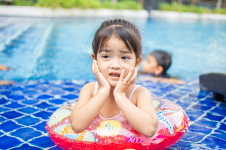 cute little girl feel happy play and swimming at swimming pool , sunny day and soft focus.