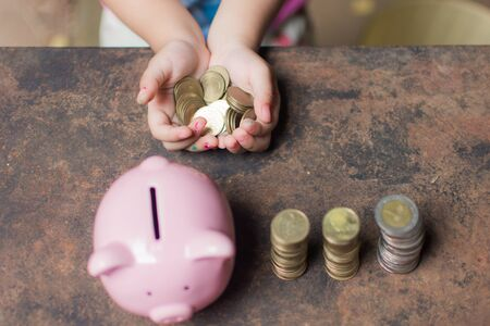 cute little girl holding coin of money and put in pink piggy bank with blur background. subject is blurred. Reklamní fotografie