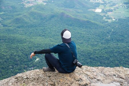 alone man sitting on the rock top of mountain and feel sad and loneliness. soft focus and noise. Reklamní fotografie